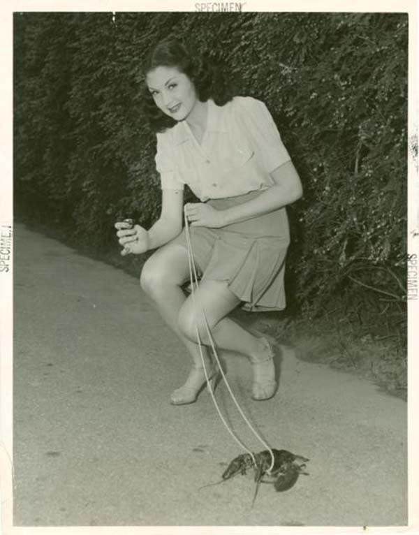 39. A young woman takes her pet lobster out for a walk (1950s).