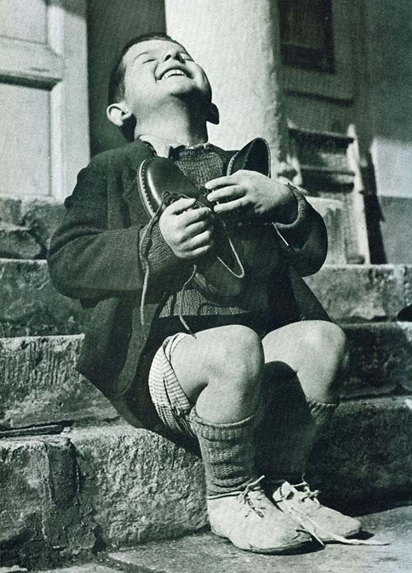 28. An Austrian boy is excited about his first pair of new shoes in years (1946).