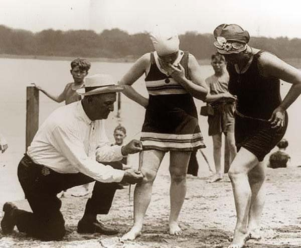 10. A beach official measures bathing suits to make sure they aren't too short (1920).
