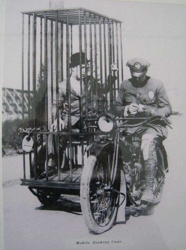 7. A police officer on a Harley-Davidson transports a prisoner in a holding cell (1921).