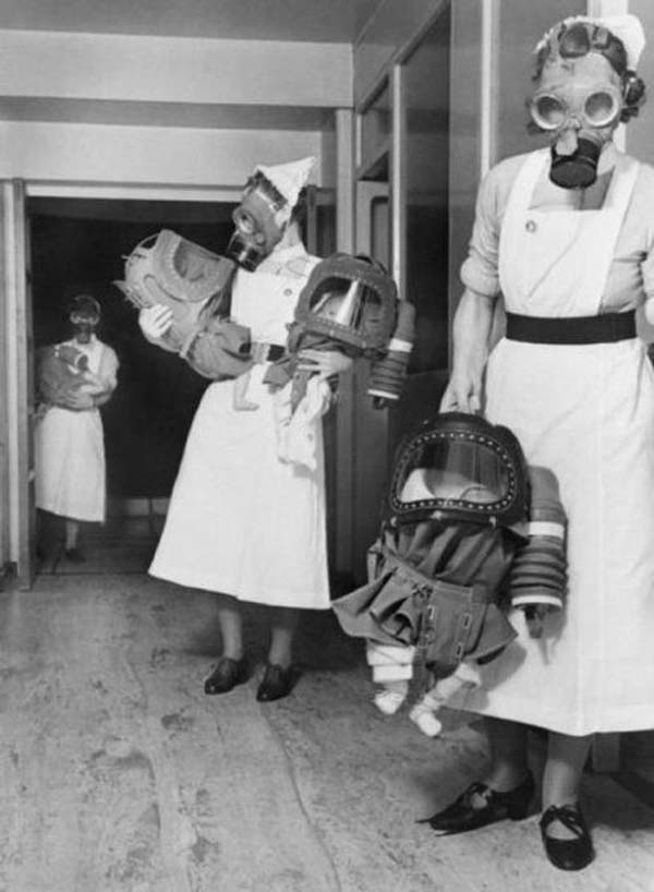 25. Infants wear gas mask hoods during a London bombing drill (1940).
