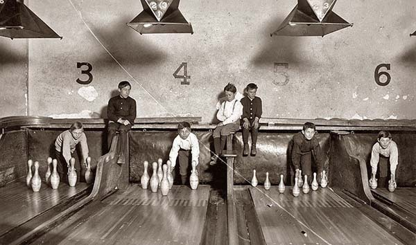 "5. ""Pin boys"" set up bowling pins while people play games (1914)."