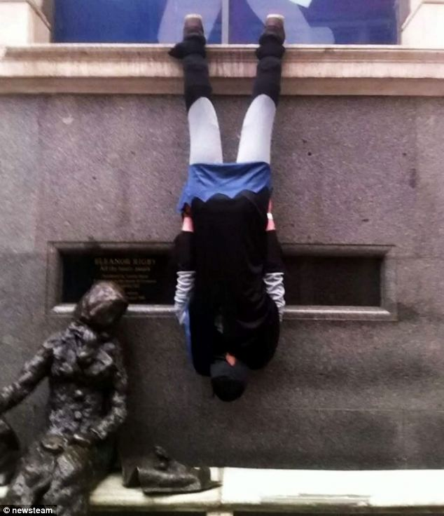joker dressed as Batman and hanging upside down by his ankles in streets at Nottingham