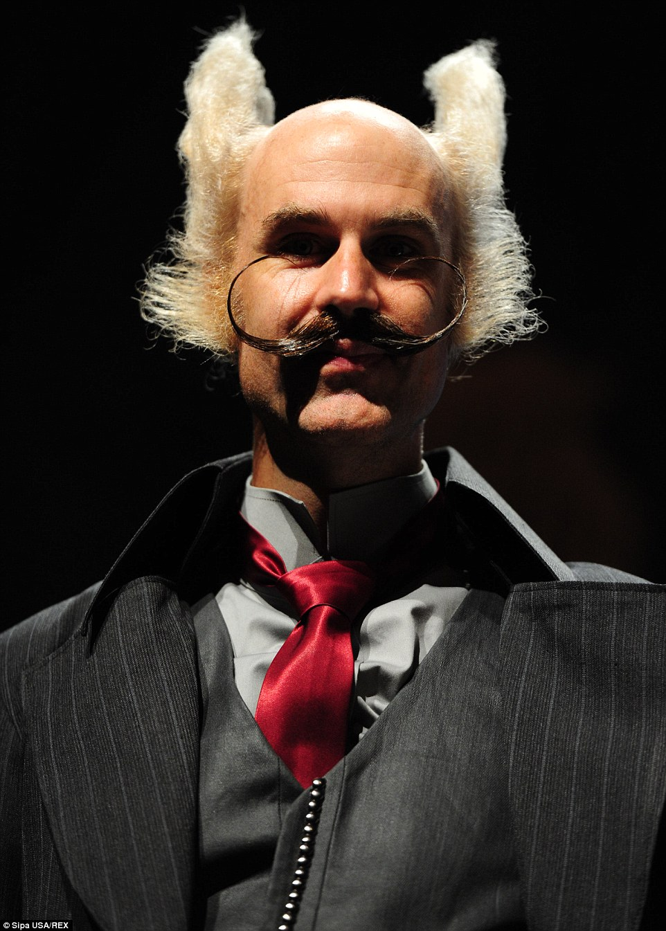 A man shows off his wispy, curved moustache and fuzzy white hair, complete with a waistcoat and tie combination