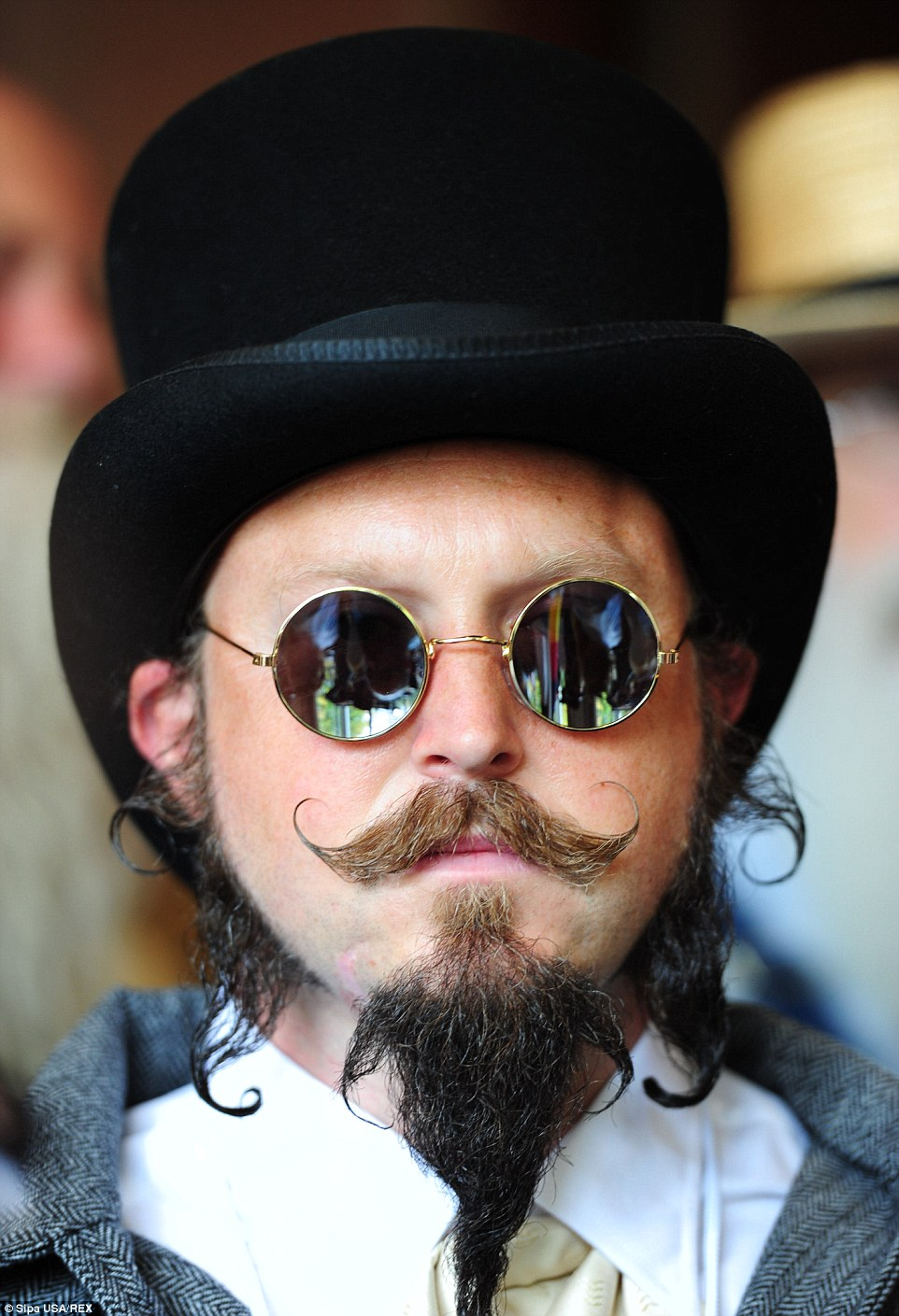 A man in a top hat shows off his well-perfected facial hair at the competition which celebrates unconventional looks