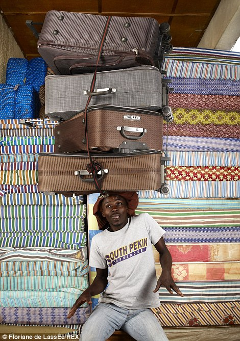 Headstrong: A man shifts his body around as he carries four large suitcases on his head