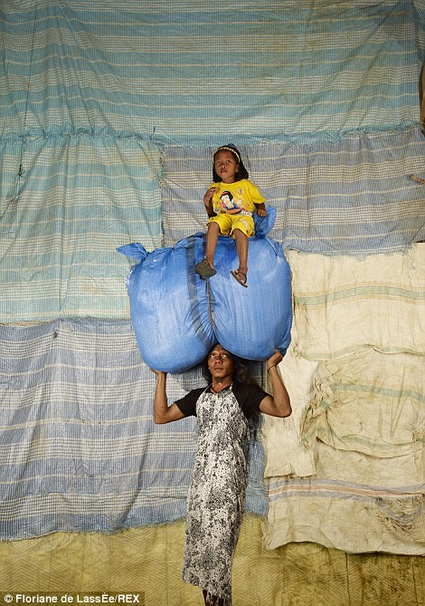 An Indonesian woman balances a huge blue sack on her head as a child sits on top