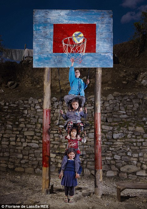 A young girl takes the strain as she carries three children on her shoulders under a basketball hoop in her native Nepal