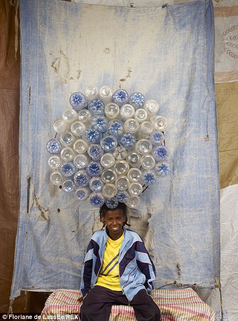 Balancing act: A child rom Teckle in Ethiopia appears untroubled by the huge bundle of water bottles he is carrying on his head