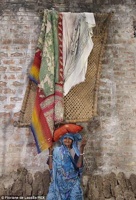 An elderly woman from India uses a small orange cushion to help her balance a large wooden structure on her head